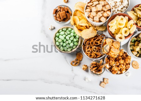 Variation different unhealthy snacks crackers, sweet salted popcorn, tortillas, nuts, straws, bretsels, white marble background copy space #1134271628