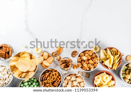 Variation different unhealthy snacks crackers, sweet salted popcorn, tortillas, nuts, straws, bretsels, white marble background copy space #1139053394