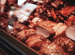 Variation of choice quality smoked meat in counter of meat shop. Close up of fridge full filled with smoked meat.