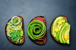 Variation of healthy rye breakfast sandwiches with avocado and toppings. toning. selective focus