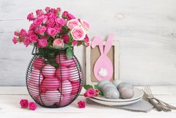 Varicolored pink Easter eggs in wire basket with roses bouquet, grey eggs in plate, silverware and rabbit in frame decor on rustic white wooden background. Table decoration.