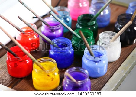 Varied colors of paints for painting in jars close up. The range of colors. Concept hobbies and hobbies. Photo close up.