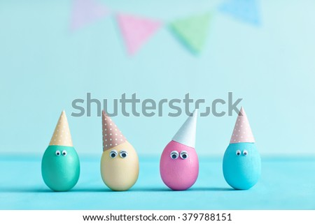 Variegated eggs in festive caps on pastel background. Interesting Easter idea. Festive garland . Colored eggs with eyes. Decoration for birthday