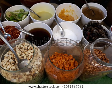 Varieties of ingredients for cooking Thai papaya salad (famous delicious food.Bean,dried salted prawn,salted crab,sugar,fish sauce,dried chili,fermented fish sauce,palm sugar,lime.Variety concept. #1059567269