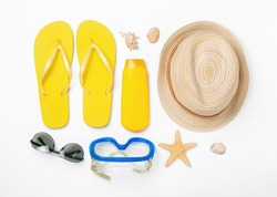 Variety beach accessories on white background. Vacation and travel items, top view