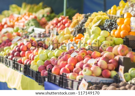 Variety of apples, oranges and grapes in boxes on city market