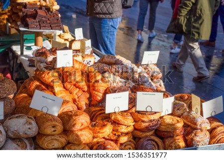 Variety of artisan pastries and breads on display for sale at a street market stall in the UK