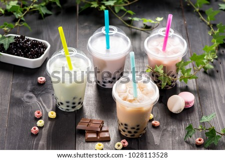 Variety of bubble tea in plastic cups with straws on a wooden table. #1028113528