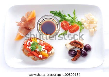 Variety of canapes on a plate; olives and sundried tomato, parma ham with rockmelon, toast with roasted mixed peppers and feta cheese, cubes of cheese and salad