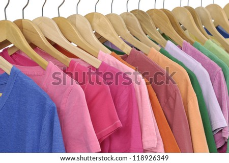 Variety of casual clothes Colors of rainbow on wooden hangers
