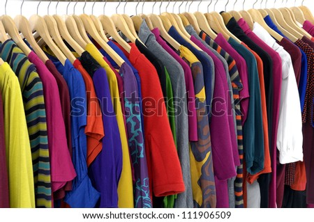 Variety of casual clothes of different colors on wooden hangers