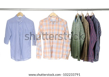 Variety of casual Man's cotton plaid shirt on wooden hangers