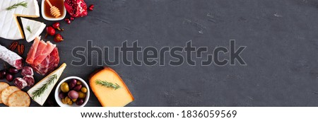 Variety of cheese and meat appetizers. Top view corner border on a dark slate banner background with copy space.