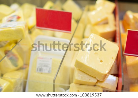 Variety of cheese pieces in supermarket