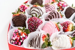 Variety of chocolate dipped strawberries in a heart-shaped box.