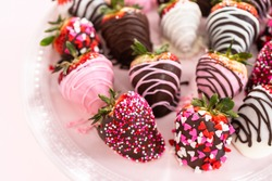 Variety of chocolate dipped strawberries on a pink cake stand.