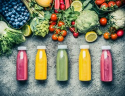 Variety  of colorful Smoothies or juices bottles beverages drinks with various fresh ingredients: fruits ,berries  and vegetables on gray concrete background , top view.  Healthy Food concept