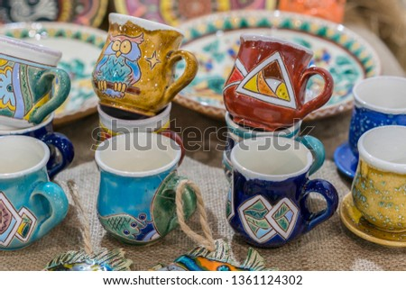 Variety of Colorfully Painted Ceramic Pots in an Outdoor Shopping Market. pottery in the shop window. Clay cups and plates