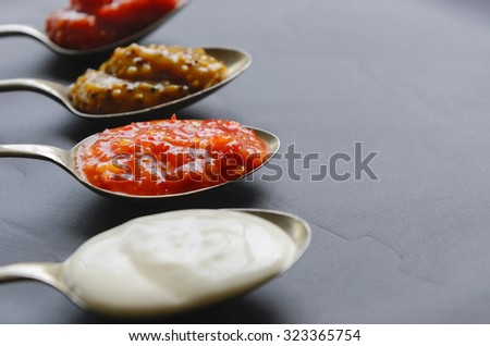 Variety of condiments on vintage spoons on slate background, mayonnaise, tomato sauce, mustard and sweet chilli jam
