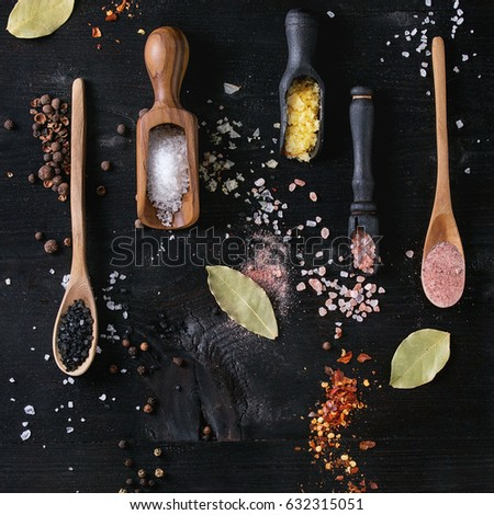 Variety of different colorful salt yellow saffron, pink, black himalayan, white sea fleur de sel in wooden spoons with chili, allspice pepper over black burnt wood background. Top view. Square image #632315051