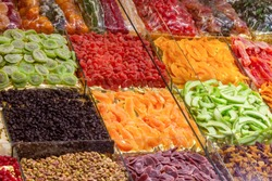 Variety of dried fruits on the market stall. Delicious colored assortment of sweet dry kiwi, mango, avocado, apricot, grapes