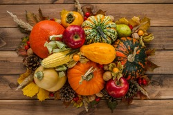 Variety of edible and decorative gourds and pumpkins. Flat lay composition of different squash types with cones, nuts, corn on the cob, kaki, rosehips, physalis peruviana fruits and autumn leaves.