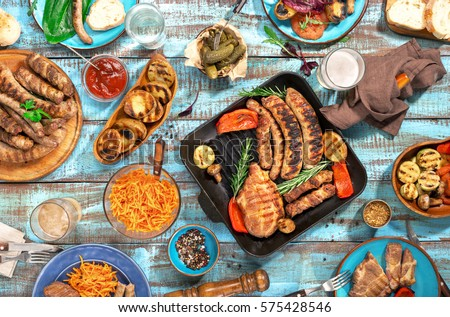 Variety of food grilled on wooden table, top view. Outdoors food Concept