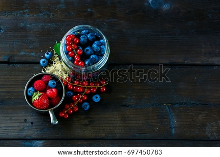 Variety of fresh berries, brown sugar and mint for making berry jam on dark rustic background, top view, copy space. #697450783