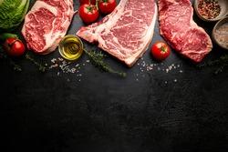 Variety of Fresh Raw Black Angus Prime Meat Steaks T-bone, New York, Ribeye and seasoning on black background, top view