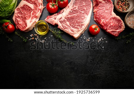 Variety of Fresh Raw Black Angus Prime Meat Steaks T-bone, New York, Ribeye and seasoning on black background, top view Stockfoto ©