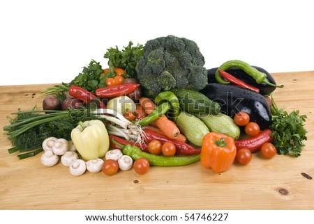 Variety of fresh vegetables garden stuff on kitchen wood table