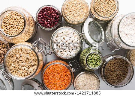 Variety of grains and legumes in glass jars, top view. Zero waste storage concept