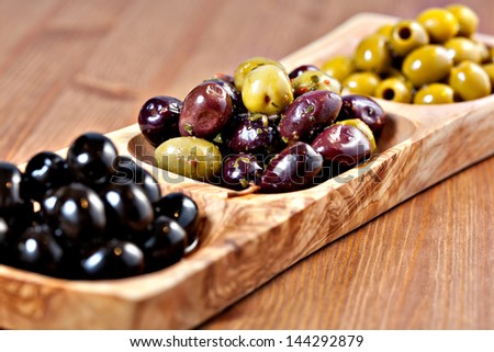 Variety of green, black and mixed marinated olives in olive tree dish on wooden table. Selective focus