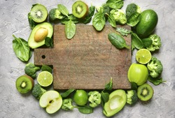Variety of green fruits and vegetables with empty wooden cutting board on a grey concrete,stone or slate background.Top view.
