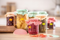 Variety of home made pickles and preserves, checkered tops and yellow labels on jars.