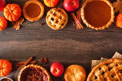 Variety of homemade autumn pies. Pumpkin, apple and pecan. Above view double border over a rustic wood background with copy space.