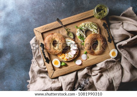 Variety of homemade bagels with sesame seeds, cream cheese, pesto sauce, eggs, radish, herbs served on wooden tray with cloth and ingredients above over blue texture background. Top view, space.