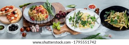 Variety of homemade prepared vegan pasta, pizza and snacks on gray background. Italian cuisine. Top view, flat lay. Panorama, banner Photo stock ©