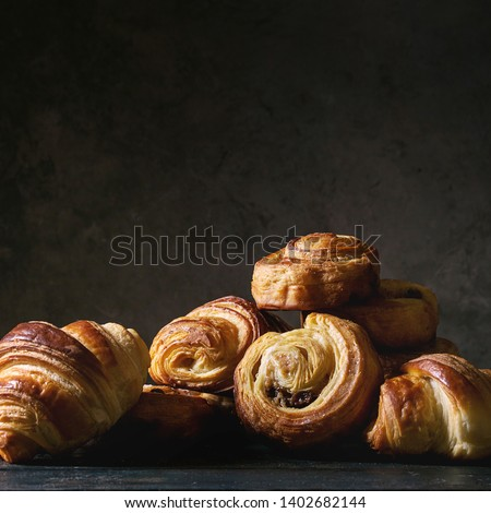 Variety of homemade puff pastry buns cinnamon rolls and croissant on wooden table. Dark still life. Copy space. Square image Stockfoto ©