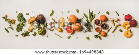 Variety of immunity boosting plant foods. Flat-lay of ginger, turmeric, kale, artichoke, citrus fruit, herbs, garlic, pepper over white background, top view. Healthy, vegan virus defeating ingredients