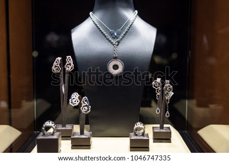 Variety of jewelry in store window. Rings, bracelets, earrings and necklaces on stands for sale. #1046747335