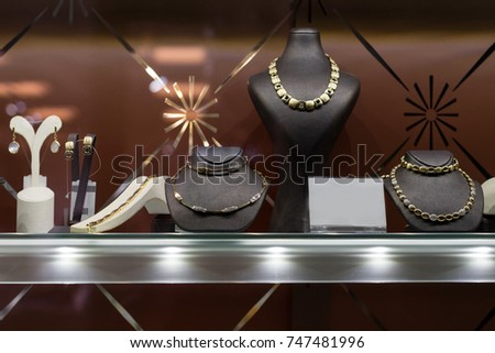 Variety of jewelry in store window. Rings, bracelets, earrings and necklaces on stands for sale #747481996