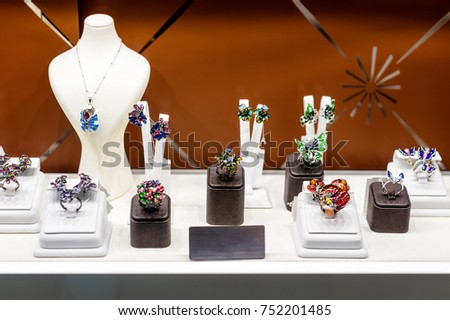 Variety of jewelry in store window. Rings, bracelets, earrings and necklaces on stands for sale #752201485