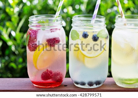 Variety of lemonade in mason jars with berries and fruits on the front porch