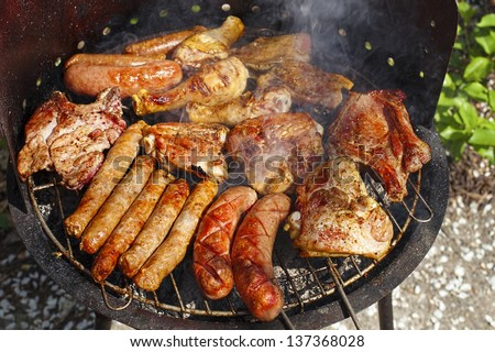 variety of meat on an outdoor, sunlit, smoking barbecue grill