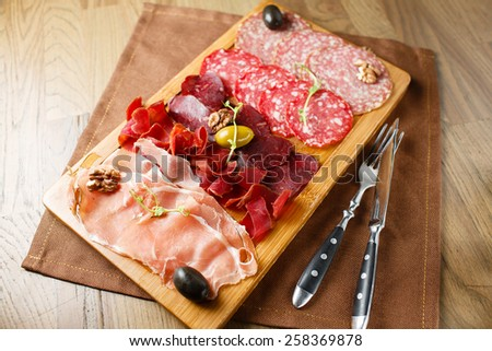 Variety of meats, sausages, salami, ham, olives, laid out on a wooden board close-up, horizontal, are next to a knife and fork