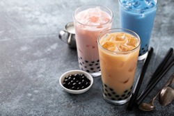 Variety of milk bubble tea in tall glasses, strawberry, butterfly tea and black
