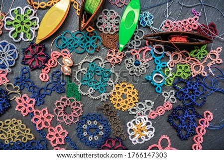 Variety of multi-colored examples of tatting lace, shuttles for weaving lace tatting with multi-colored threads and beads on a dark gray stone background. Tatting is a kind of elite needlework. Photo stock ©