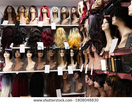 Variety of natural wigs and hairpieces hanging on stand in specialized store
