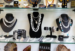 Variety of necklaces, bracelets and earrings made of white and black pearls on mannequins in jewelry store window..
